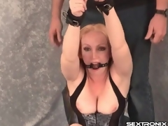 Fastened and gagged milf in tight corset